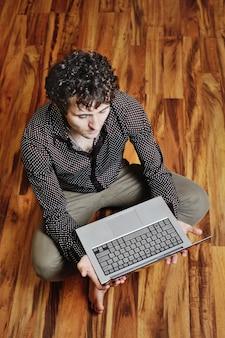Ein junger mann mit einem laptop auf dem hintergrund des bretterbodens