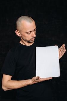 Ein junger mann mit einem leeren weißen banner. eine person hält ein werbeblatt, einen kopierraum, isoliert