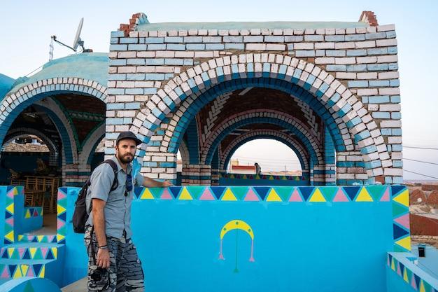 Ein junger mann mit einem rucksack auf einer schönen terrasse eines traditionellen blauen hauses in einem nubischen dorf nahe der stadt assuan. ägypten