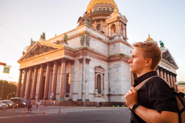 Ein junger mann mit einem rucksack steht vor dem hintergrund der isaakskathedrale in st. petersburg