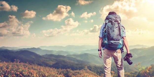 Ein junger mann mit einem rucksackreisenden, der auf einer klippe steht
