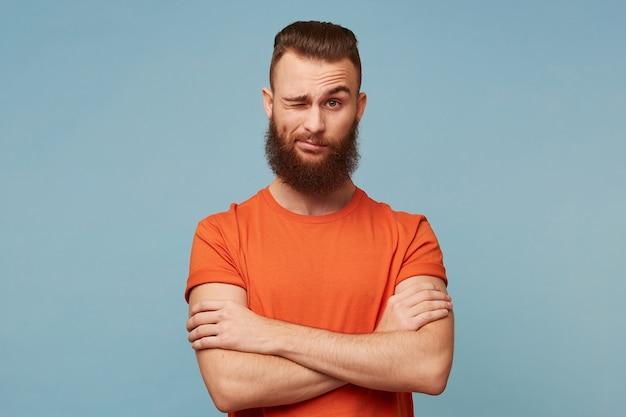 Ein junger mann mit einem schönen dicken bart gekleidet in einem roten t-shirt, das auf blau lokalisiert wird