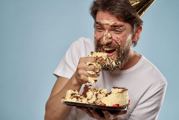 Ein junger mann mit einer geburtstagstorte fiel mit einer torte auf sein gesicht, sein gesicht mit einer torte