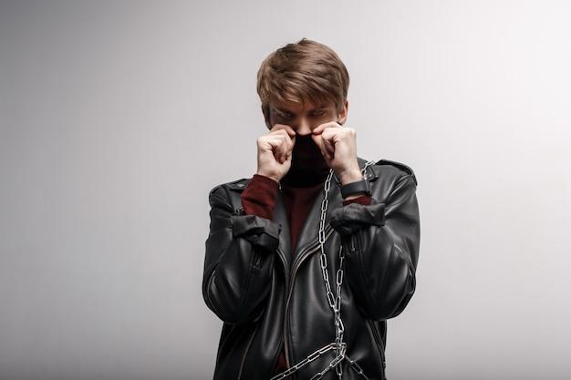 Ein junger mann mit einer modischen frisur im roten golf in einer lederjacke in schwarzen jeans bedeckt sein gesicht mit den händen und schaut in die kamera im studio in der nähe einer weißen wand. attraktiver süßer kerl.