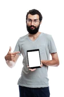 Ein junger mann mit einer tablette zeigt auf einem isolierten bildschirm.