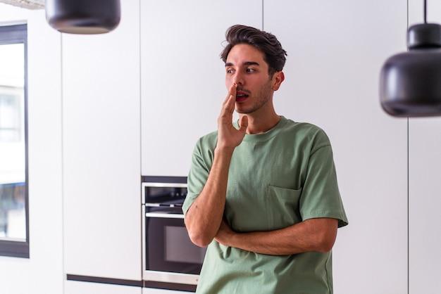 Ein junger mann mit gemischten rennen in seiner küche sagt eine geheime heiße bremsnachricht und schaut beiseite
