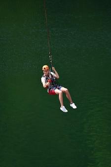 Ein junger mann mit helm ist vom bungee-jumping gesprungen und hängt jetzt an einem seil, schwingt und filmt sich auf einer sportvideokamera vor einem verschwommenen wasserhintergrund