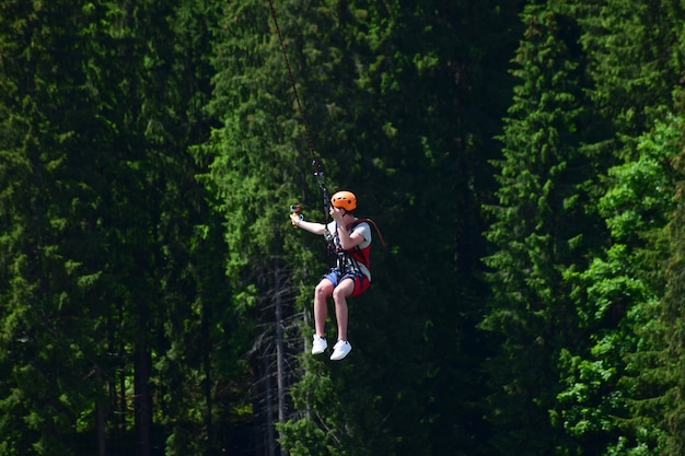 Ein junger mann mit helm sprang vom bungee-jumping und hängt jetzt an einem seil, schwingt und filmt sich auf einer sportvideokamera vor einem verschwommenen hintergrund eines grünen waldes