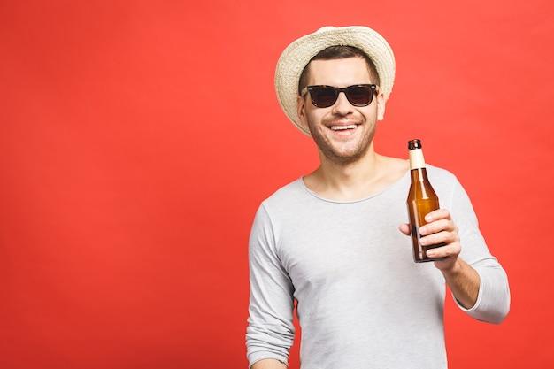 Ein junger mann mit hut und sonnenbrille hält eine flasche bier