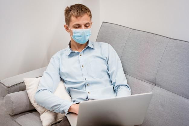 Ein junger mann mit kaukasischem aussehen in blauem hemd und schutzmaske mit laptop auf der couch...