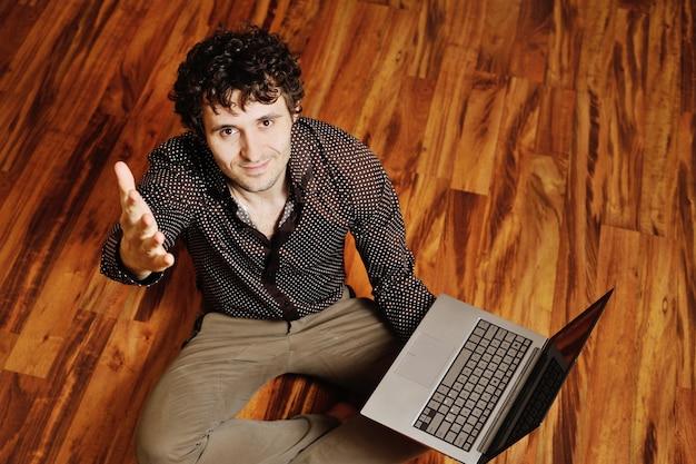 Ein junger mann mit lockigem haar sitzt an einem laptop auf dem warmen boden. kreative idee, schöpfer, designer