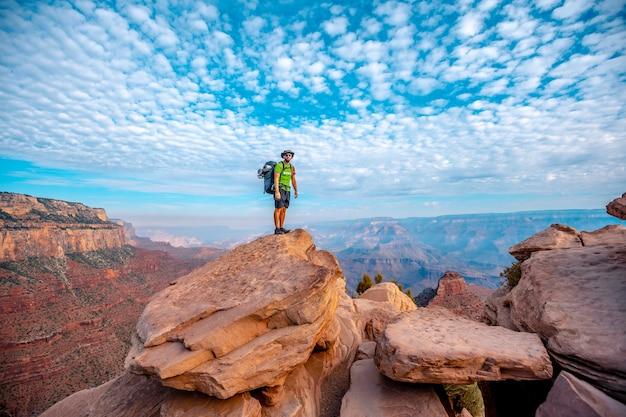 Ein junger mann mit offenen armen auf einem aussichtspunkt des abstiegs des south kaibab trailhead. grand canyon, arizona