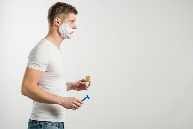 Ein junger mann mit rasierschaum auf seinen wangen, die bürste und rasiermesser gegen grauen hintergrund halten