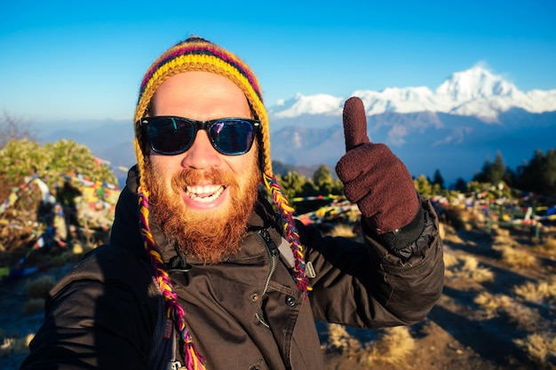 Ein junger mann mit rotem bart und rucksack in den bergen macht ein selfie. das konzept der aktiven erholung und des tourismus in den bergen. nepal im frühjahr.