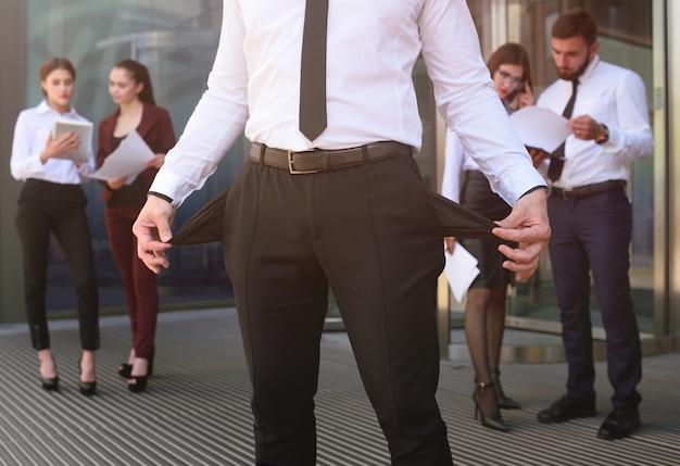 Ein junger mann mit seinen taschen stellte sich gegen das büro