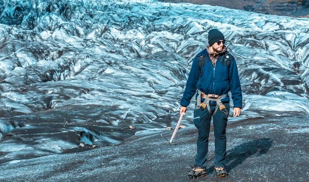 Ein junger mann mit stiefeln und hammer auf dem trekking des svinafellsjokull-gletschers. island