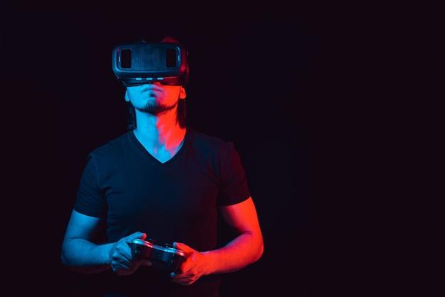 Ein junger mann mit virtual-reality-brille spielt videospiele