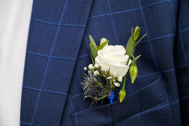 Ein junger mann oder bräutigam in einem weißen hemd, einer fliege und einer blau karierten weste oder jacke. schöner boutonniere aus weißen rosen und grünen blättern in einer westentasche oder einem revers. thema hochzeit.