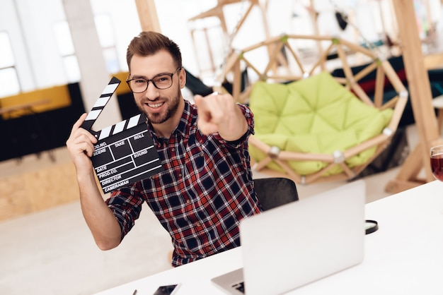 Ein junger mann posiert mit einem filmklöppel auf einer kamera.