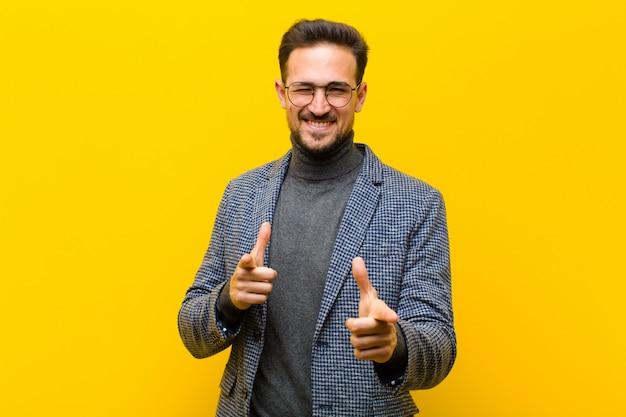 Ein junger mann posiert, während er sich glücklich und cool fühlt und dich auswählt