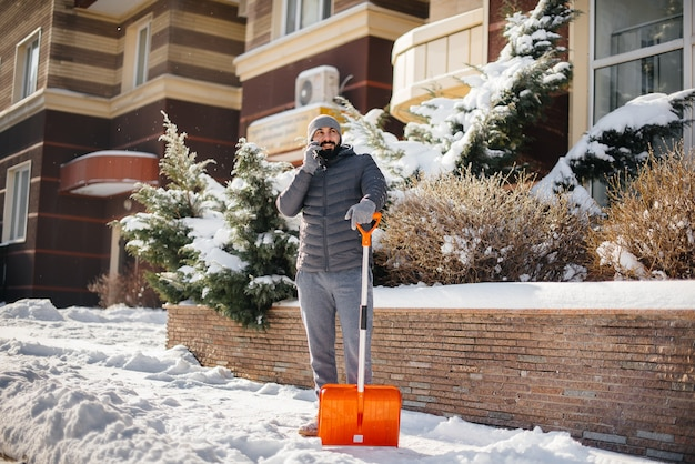 Ein junger mann räumt an einem sonnigen und frostigen tag den schnee vor dem haus ab und telefoniert.