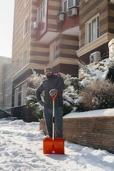 Ein junger mann räumt an einem sonnigen und frostigen tag den schnee vor dem haus ab.