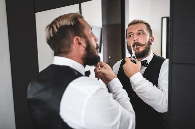 Ein junger mann rasiert sich mit einer schere den bart