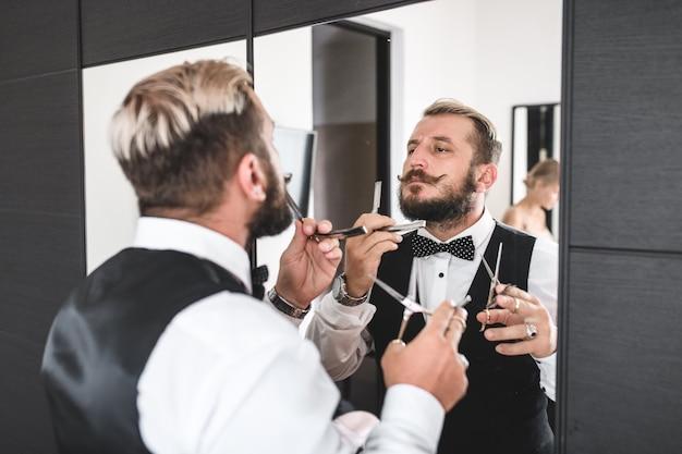 Ein junger mann rasiert sich mit einer stahlklinge den bart