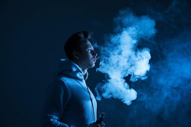 Ein junger mann raucht im studio bei neonlicht einen vape.
