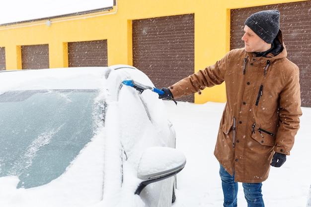 Ein junger mann reinigt schnee von seinem auto. autopflege im winter