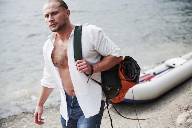 Ein junger mann reist mit einem rucksack mit einem boot. die lebensweise des reisens und der natur mit der natur