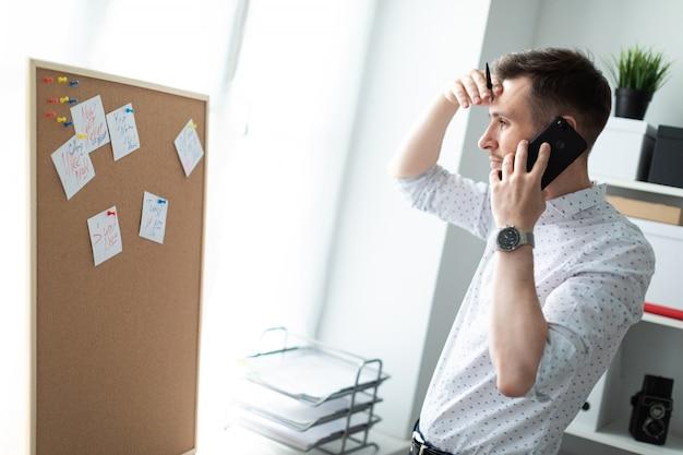 Ein junger mann schaut auf die tafel mit aufklebern und spricht am telefon.
