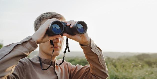 Ein junger mann schaut durch ein fernglas auf eine schöne hügelige landschaft. das konzept der jagd, des reisens und der erholung im freien. banner mit kopienraum. ein reisender oder jäger beobachtet durch ein fernglas.