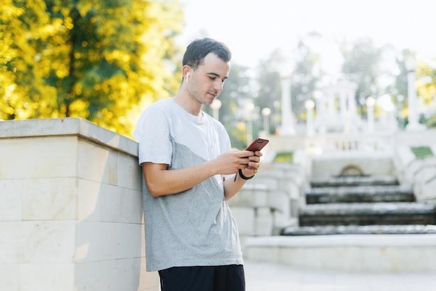 Ein junger mann schaut ins telefon und hört die musik im park.