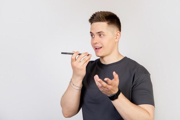 Ein junger mann schreibt eine sprachnachricht oder eine notiz in eine smartphone-anwendung