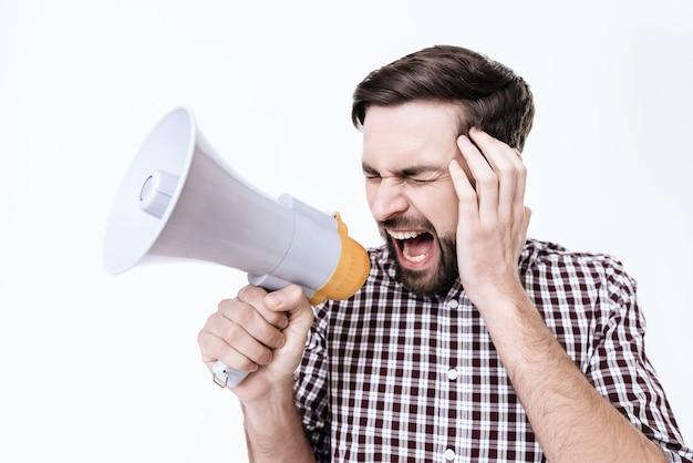 Ein junger mann schreit. er hat kopfschmerzen. er fühlt sich sehr schlecht