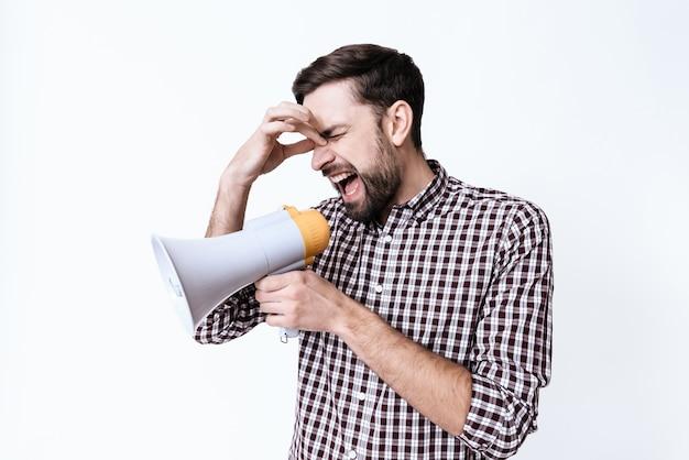 Ein junger mann schreit vor schmerzen in ein megaphon.