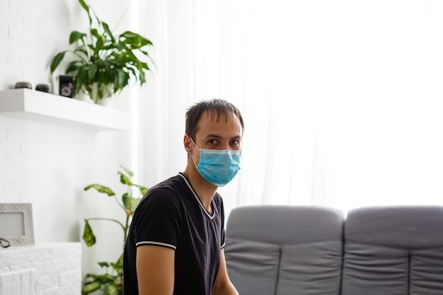 Ein junger mann setzt zum schutz vor der epidemie eine medizinische maske auf, ein nahaufnahmeporträt. schutz vor der coronavirus-pandemie.
