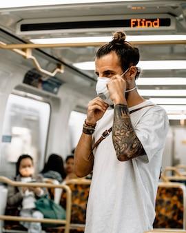 Ein junger mann setzte eine maske auf, um eine coronavirus-infektion zu vermeiden