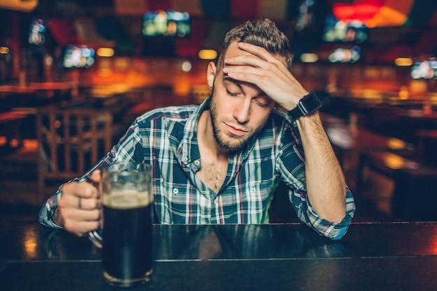 Ein junger mann sitzt allein an der theke in der kneipe. er hält einen becher dunkles bier in der hand und schaut nach unten. junger mann hat kater.