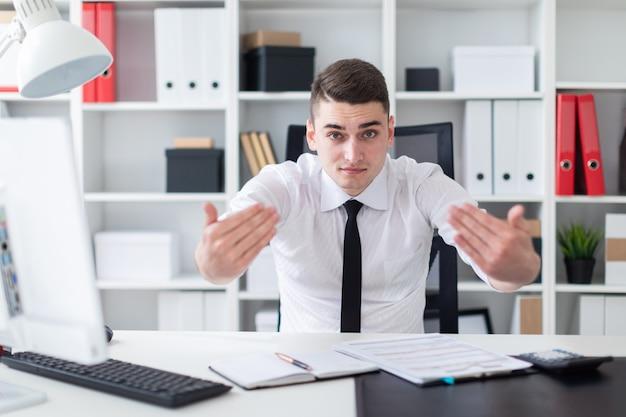 Ein junger mann sitzt an einem computertisch im büro und breitete die hände zur seite aus.