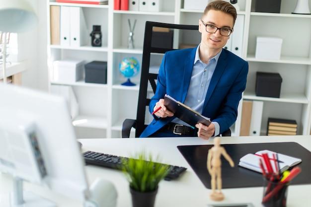 Ein junger mann sitzt an einem tisch im büro und hält dokumente und einen stift in den händen.
