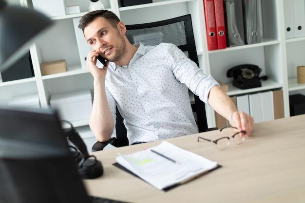 Ein junger mann sitzt an einem tisch, telefoniert und hält eine brille in der hand.