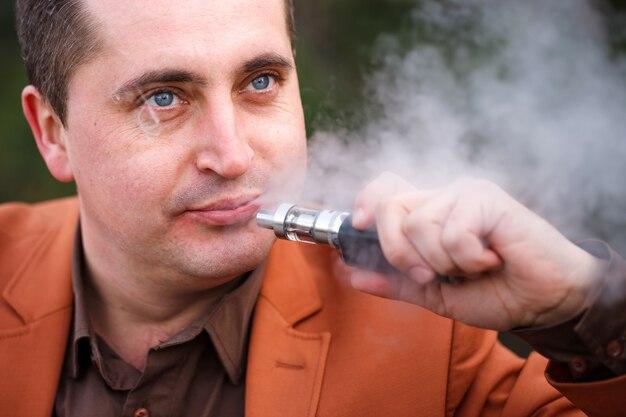 Ein junger mann sitzt auf einer bank und raucht eine elektronische zigarette.