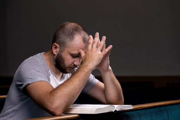 Ein junger mann sitzt auf einer kirchenbank, liest die bibel und betet.