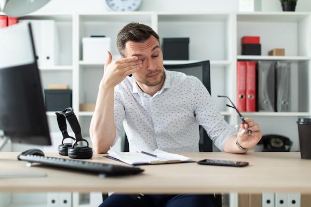 Ein junger mann sitzt im büro an einem tisch, nimmt die brille ab und reibt sich die augen.