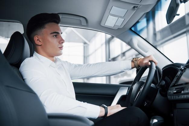 Ein junger mann sitzt in einem neu gekauften auto am steuer, ein erfolgreicher kauf.