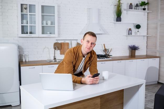 Ein junger mann sitzt mit einem laptop in der küche und telefoniert. heimarbeit.