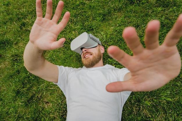 Ein junger mann spielt ein spiel in gläsern der virtuellen realität, die im gras liegen.