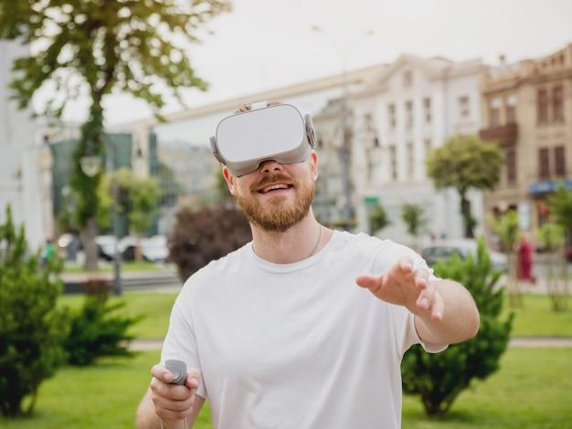 Ein junger mann spielt ein spiel mit einer virtual-reality-brille auf der straße.
